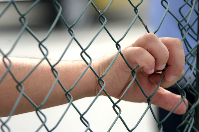 A hand gripping a wire fence